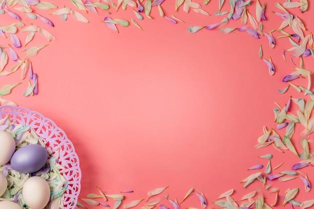 Pisanki i kolorowe płatki wiosennych kwiatów na jasnoróżowym ciepłym tle.