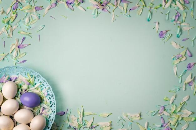 Pisanki i kolorowe płatki wiosennych kwiatów na jasnozielonym tle.