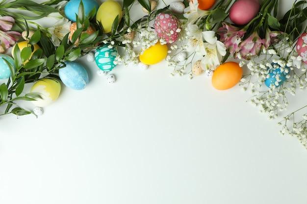 Pisanki i piękne kwiaty na białym tle, miejsce na tekst