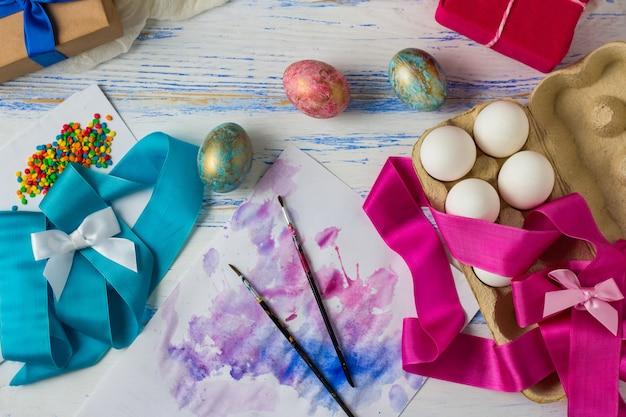 Pisanki i proces barwienia jajek przed świętem. taśmy, jajka, pędzle, prezenty na białym drewnianym stole