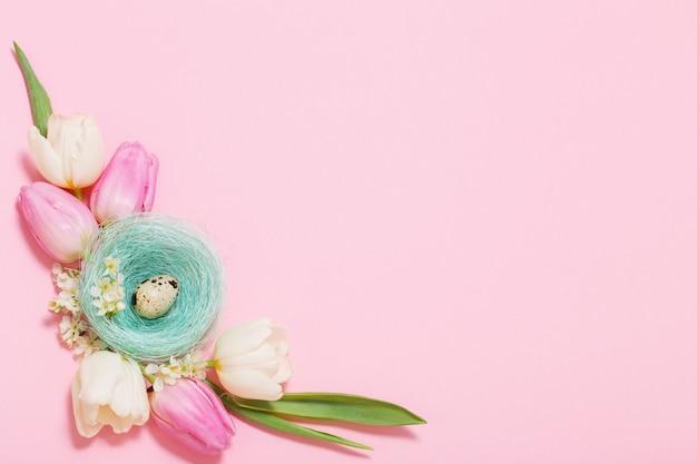 Pisanki i wiosenne kwiaty na różowej powierzchni