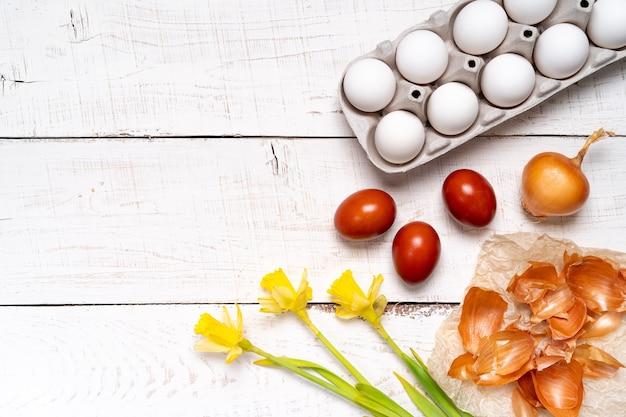 Pisanki maluje się naturalnym barwnikiem jajecznym z owoców i warzyw, jajka maluje się łuskami cebuli na białym drewnianym stole i żółtych żonkilach, miejsce na kopię