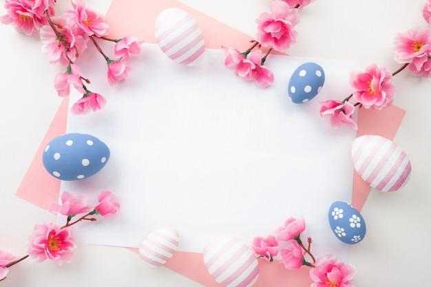Pisanki na różowym tle. wiosenne kwiaty dla karty wesołych świąt. widok z góry na płasko.