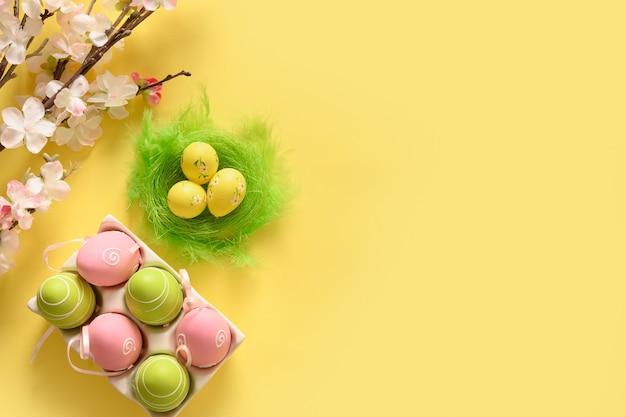 Pisanki pastelowe w żółtym kartoniku i wiosenne kwitnące kwiaty na żółto.