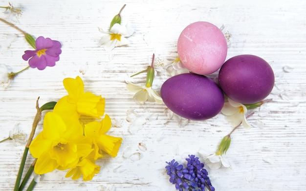 Pisanki pomalowane na różowo i fioletowo na stole wśród wiosennych kwiatów i bukietu żonkili