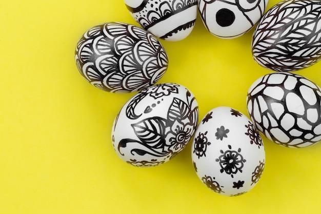 Pisanki są pomalowane na czarno-biało, abstrakcja, ułożone w okrąg. malowane pisanki na żółtym tle. leżał płasko. skopiuj miejsce z bliska