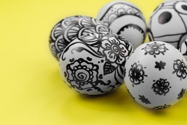 Pisanki są pomalowane na czarno-biało, abstrakcja, ułożone w okrąg. malowane pisanki na żółtym tle. ścieśniać. skopiuj miejsce