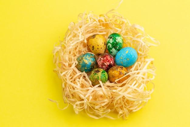 Pisanki są pomalowane na czerwono, żółto, niebiesko i zielono. jajka są w gnieździe z wiórów drzewnych. malowane pisanki na żółtym tle. mieszkanie leżał. skopiuj miejsce