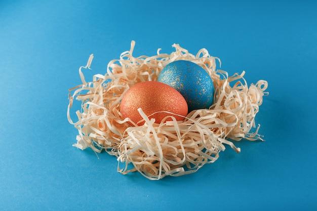 Pisanki są pomalowane na niebiesko złotem i pomarańczowo na złoto. dwa jajka leżą w gnieździe wiórów drzewnych. malowane pisanki na niebieskim tle. skopiuj miejsce