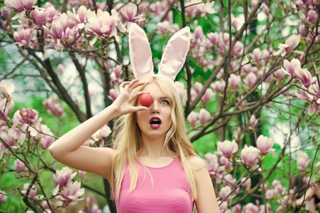 Pisanki u kobiety w uszach królika. wesołych świąt koncepcja, kobieta w kwitnących kwiatach magnolii, wiosna