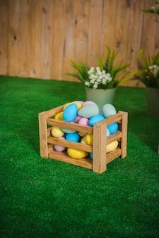 Pisanki w drewnianym pudełku i wielkanocna dekoracjakoncepcja kartki z życzeniami kolorowe jajko