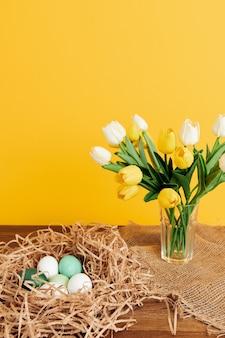 Pisanki w gnieździe bukiet kwiatów dekoracji wiosennych wakacji