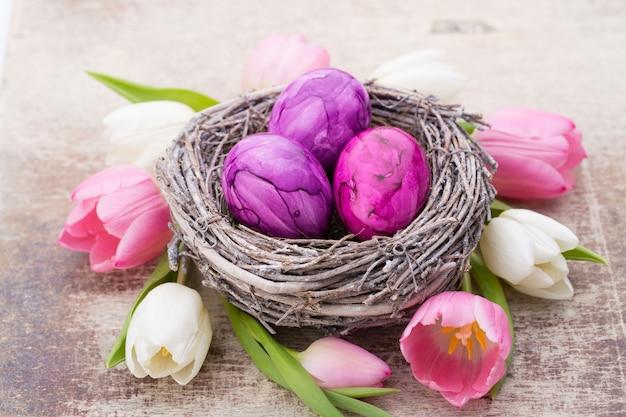 Pisanki w gnieździe z tulipanami dookoła