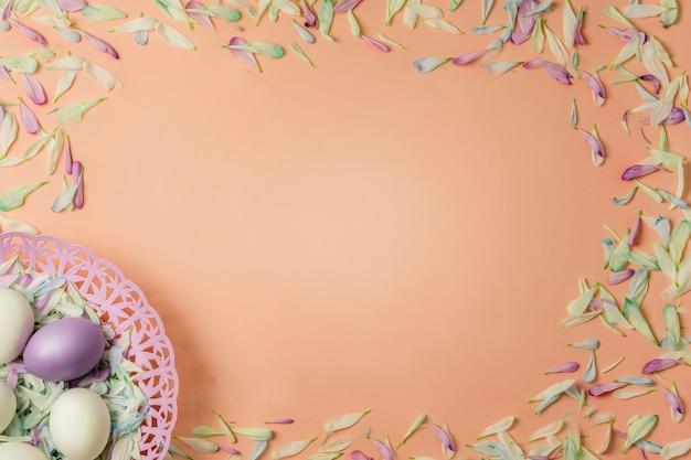 Pisanki w koszu i kolorowe płatki wiosennych kwiatów rumianku i chryzantemy na jasnożółtym ciepłym musztardowym tle.