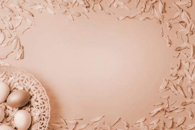Pisanki w koszu i kolorowe płatki wiosennych kwiatów rumianku i chryzantemy na piaskowatej kremowej musztardzie modne matowe tło.