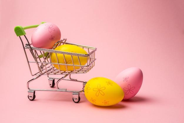 Pisanki w koszyku na jasnoróżowym tle. szablon promocji i zakupów na wielkanoc. latające jajka.