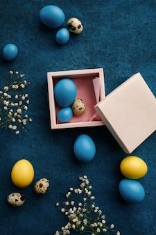 Pisanki w pudełku prezentowym na niebieskim tle tkaniny
