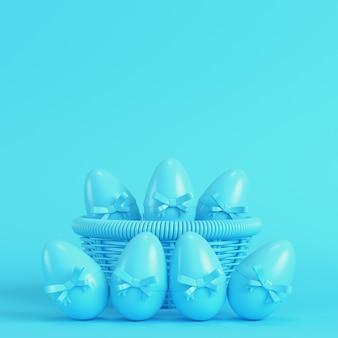 Pisanki z kokardą w wiklinowym koszu na jasnoniebieskim tle w pastelowych kolorach. koncepcja minimalizmu