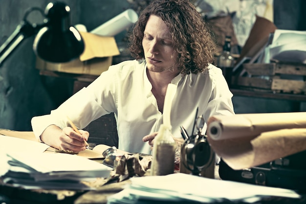 Pisarz w pracy. przystojny, młody pisarz siedzi przy stole i pisze coś w swoim szkicowniku w domu