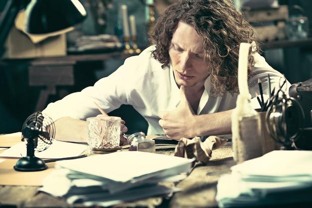 Pisarz w pracy. przystojny, młody pisarz siedzi przy stole i pisze coś w swoim szkicowniku