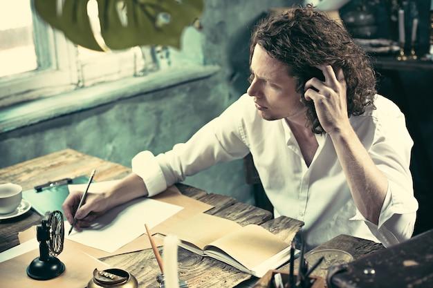 Pisarz w pracy. przystojny młody pisarz siedzi przy stole i pisze coś w swoim szkicowniku