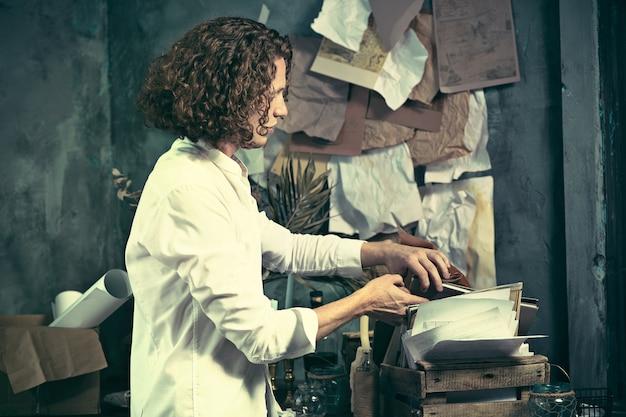 Pisarz w pracy. przystojny młody pisarz stojący przy stole i wymyślający coś w swoim umyśle