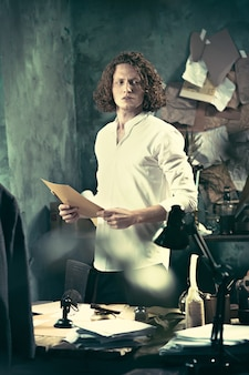 Pisarz w pracy. przystojny młody pisarz stojący przy stole i zastanawiający się nad czymś