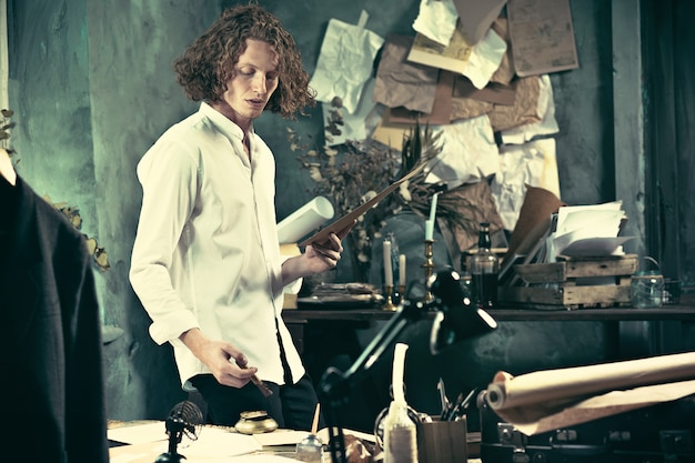 Pisarz w pracy. przystojny młody pisarz stojący przy stole i zastanawiający się w domu