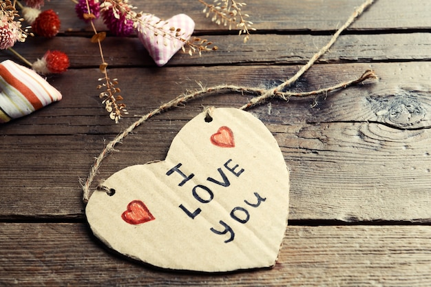 Pisemna wiadomość z suchymi kwiatami i ozdobnymi sercami na drewnianym stole z bliska