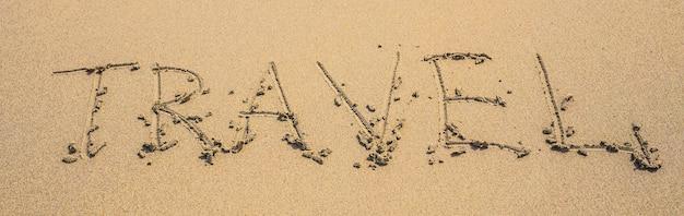 Pisemne słowa podróżują po piasku plaży w letni dzień