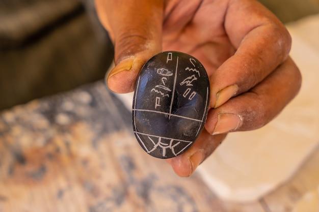 Pismo egipskie hieroglifami na czarnym alabastrowym skarabeuszu w luksorze. egipt