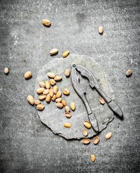 Pistacje i dziadek do orzechów na kamiennym stole