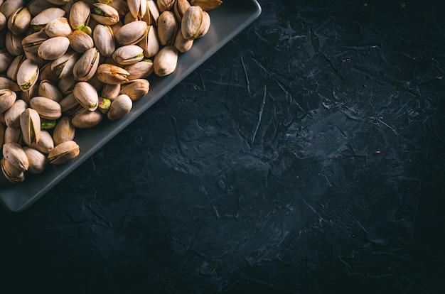 Pistacje w szarym prostokątnym talerzu na ciemnym stole