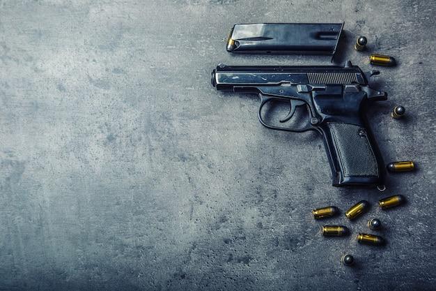 Pistolet 9mm i naboje porozrzucane na stole.