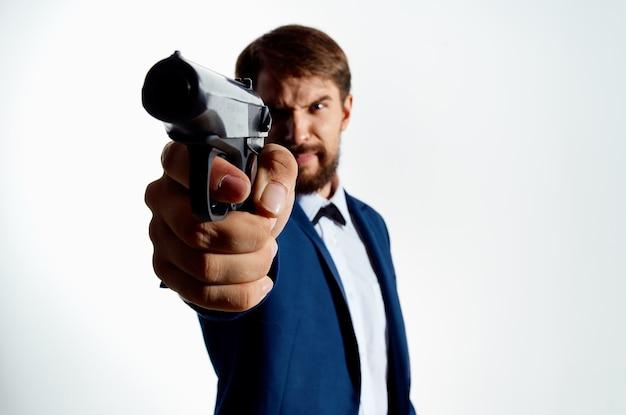 Pistolet człowieka w rękach emocji mafii agent jasnym tle. zdjęcie wysokiej jakości