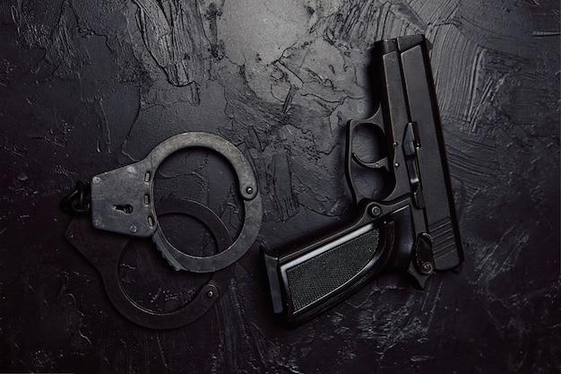 Pistolet i kajdanki na czarnym teksturowanym stole amunicja organów ścigania broń palna dla po...