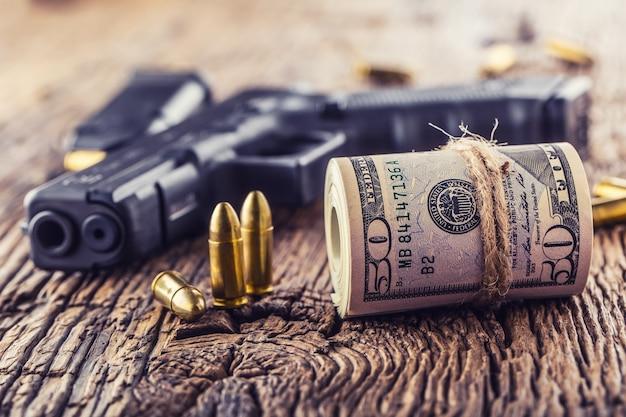 Pistolet i pieniądze. 9 mm pistolet pistoletowy naboje porozrzucane i rolowane banknoty dolarowe na rustykalnym dębowym stole.