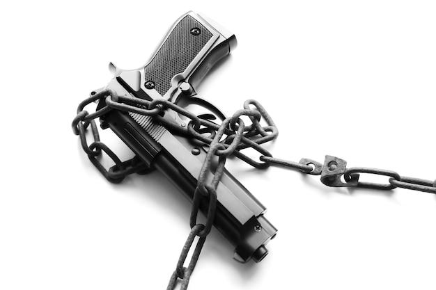 Pistolet i pieniądze w starych zardzewiałych łańcuchach. aresztowany za nielegalne przestępstwo. złamać prawo. pojęcie karne.