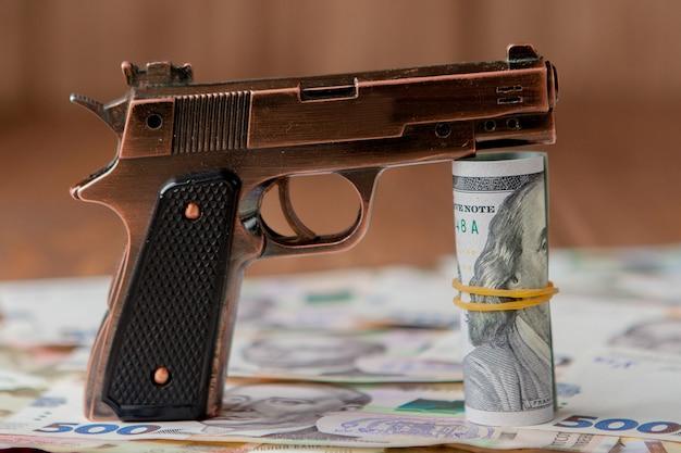 Pistolet i stos pieniędzy leżących na hrywnach na drewnianym stole. pojęcie używania narkotyków, przestępczości, uzależnienia i nadużywania substancji