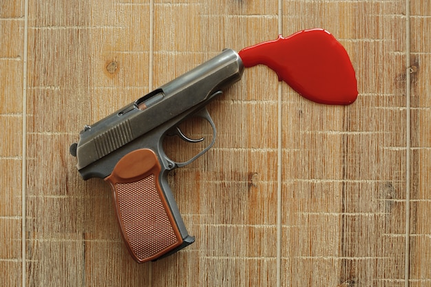 Pistolet i szkarłatna krew na desce.