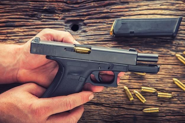 Pistolet ładujący. mężczyzna ręce ładują pistolet 9mm.