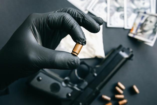 Pistolet leżący na stole. mężczyzna w czarnych rękawiczkach trzymający kule. nielegalna sprzedaż narkotyków. problemy kryminalne. dolary.