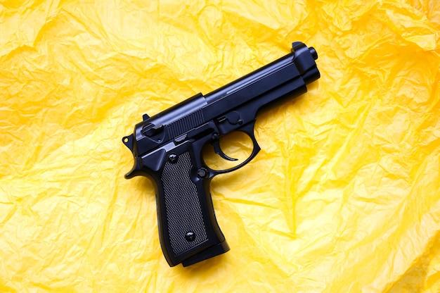 Pistolet leżący na żółtym tle. legalizacja broni. pojęcie zbrodni.