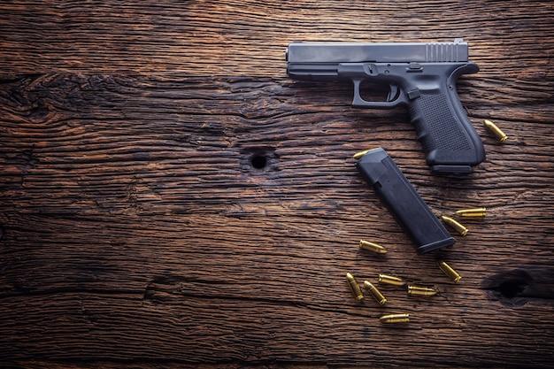 Pistolet pistoletowy. pistolet 9 mm i naboje rozrzucone na rustykalnym dębowym stole.