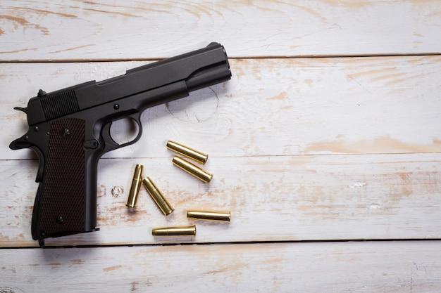 Pistolet ręczny z pociskami na drewnianym biurku