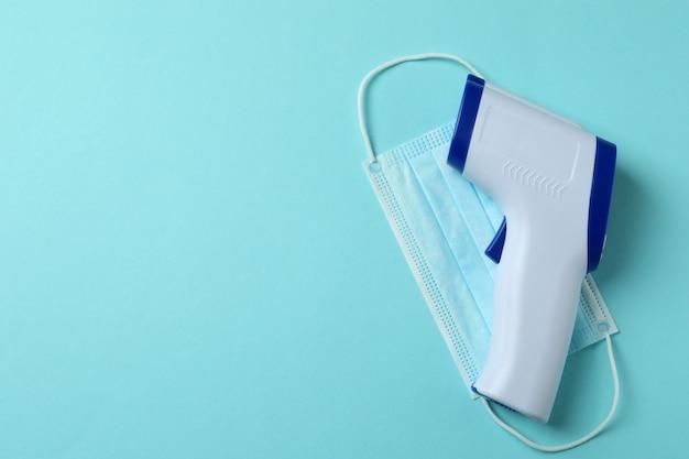 Pistolet termometr i maska medyczna na niebiesko
