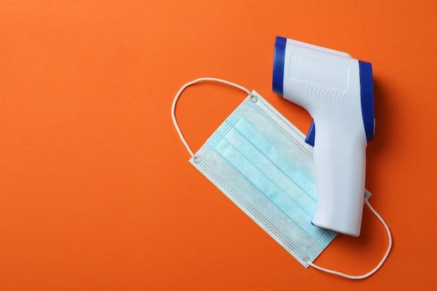 Pistolet termometryczny i maska medyczna na pomarańczowo