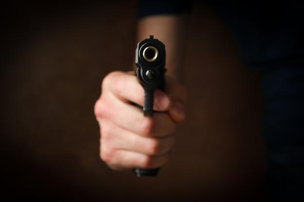 Pistolet trzymaj człowieka. selektywne ustawianie ostrości. bandyta. przemoc