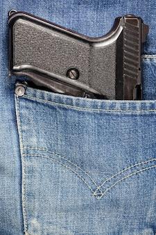 Pistolet w kieszeni dżinsów.