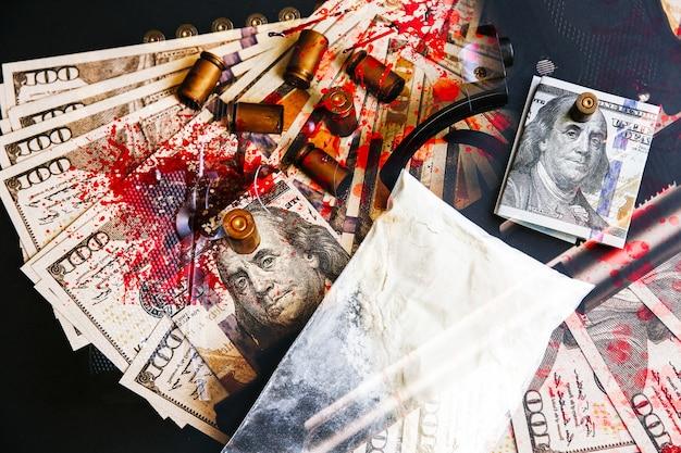Pistolet z kulami leżącymi na stole. plamy krwi. problemy kryminalne. leki i pieniądze na czarnym tle. nielegalna sprzedaż.